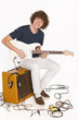 Full length male with his electric guitar sitting on amplifier
