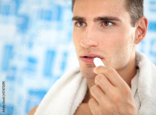 man  applying balsam for lips