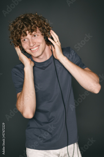 Smiling redheaded man in casual clothes with headphones