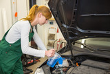 Female mechanic fills coolant or cooling fluid in motor of a car