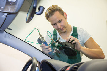 Windscreen repair by glazier after stone-chipping damage