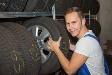 Mechanic in wheel or tire storehouse of a garage