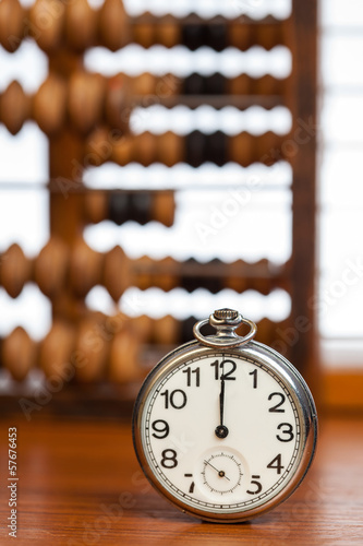 Pocket watch on table against wooden abacus