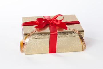 Goldenes Geschenk mit roter Schleife