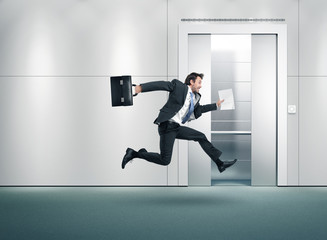 Running businessman and open lift door