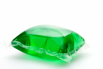 One green laundry detergent capsule on white