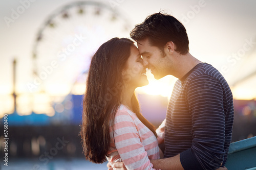 romantic couple in front of santa monica amusement park
