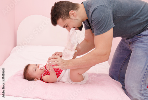 Dad changing baby diapers