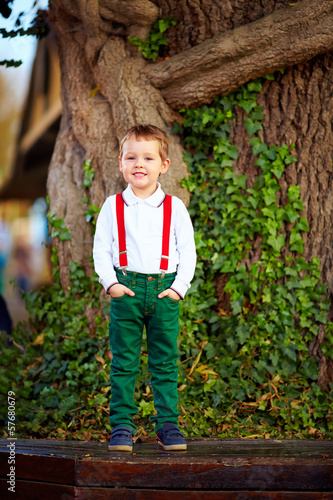 cute boy posing in front of old tree