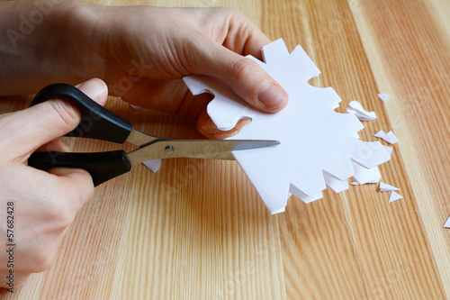 Using scissors to cut out a paper snowflake shape