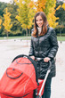 Young mother with baby in stroller in park