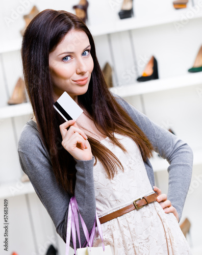 Lady hands credit card in footwear shop