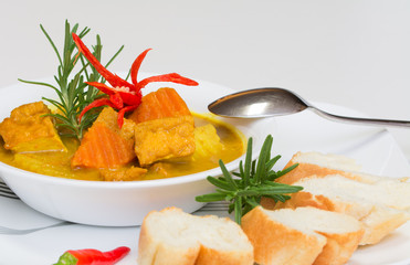 Hot, delicious tofu curry served with breads on white background