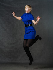 Success - young active businesswomen jumping in blue dress.
