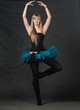 young beautiful dancer with blond hair dancing on a dark studio
