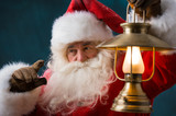 Santa Claus is holding a shining lantern outdoors at North Pole