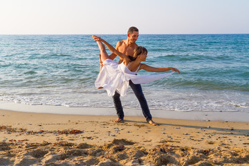 Young couple practicing a dance scene at the beach.