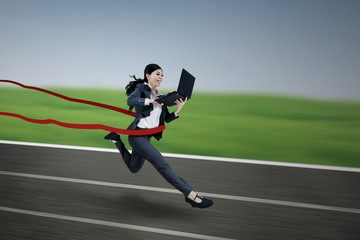 Executive businesswoman running and holding laptop