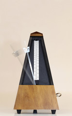 Metronome with Blurred Moving Arm Brown Background