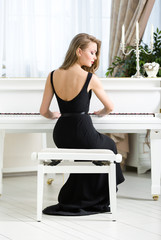 Back view of woman playing piano. Concept of music and leisure