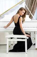 Back view of woman playing piano. Concept of music and art