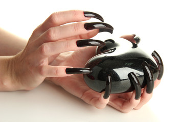 Hands with scary manicure holding black heart , isolated