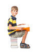 Schoolboy is sitting on books. Back to school
