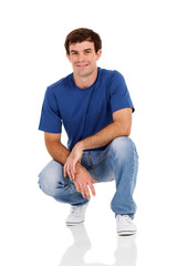 casual man squatting on white
