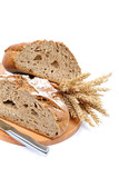 Two halves a loaf of rye bread with a knife and wheat ears.