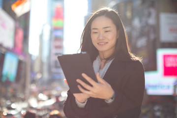 Asian woman in New York City using ipad tablet pc