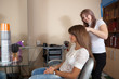 Female stylist works on woman hair