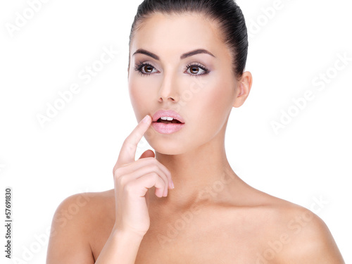 Face of a Pretty young woman with finger at  lips