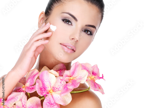 woman applying cosmetic cream on face with pink flowers on body