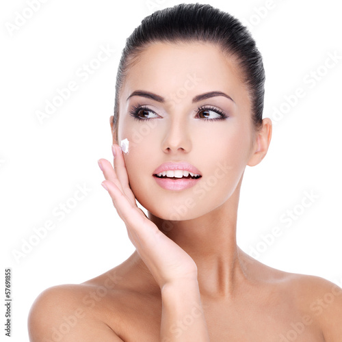 Young woman with cosmetic cream on face