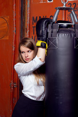 Girl in a suit near punch bag