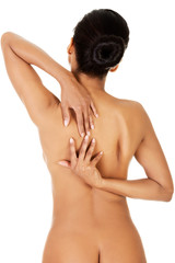 Beautiful and naked woman trying to touch her hands on her back.