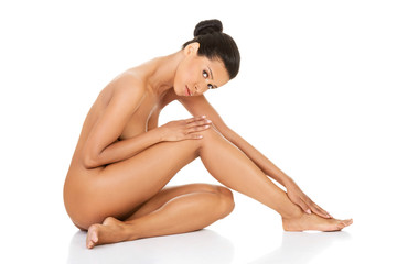 Beautiful and naked woman sitting. Side view.