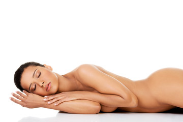 Beautiful naked woman laying on the floor.