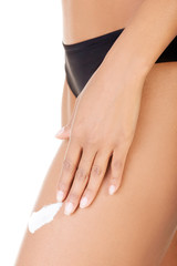 Female smooth legs with one hand lotioning. Closeup.