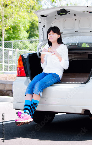 Preteen girl sitting on back car bumper eating lunch