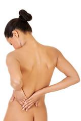Beautiful naked woman. She's touching her back.