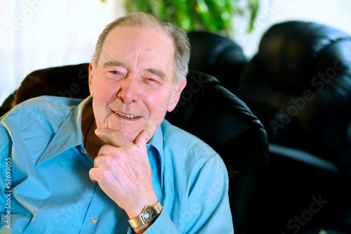 Happy Elderly man in eighties laughing in leather recliner