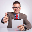 young business man with tablet shows thumb up gesture