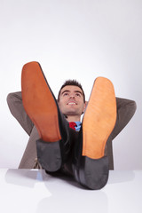 young business man looks up with hands behind head and feet on d