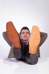 young business man sleeps with feet on desk