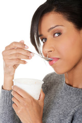 Young woman eating yogurt as healthy breakfast or snack.