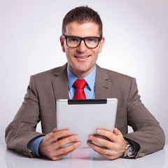 young business man with tablet smiles for you