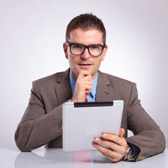 young business man with tablet holds hand on chin
