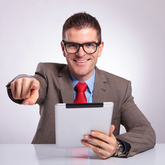 young business man with tablet points at you and smiles