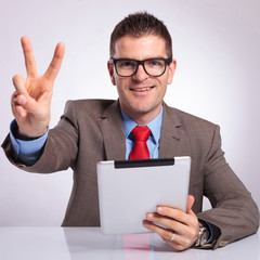 young business man with tablet shows victory sign